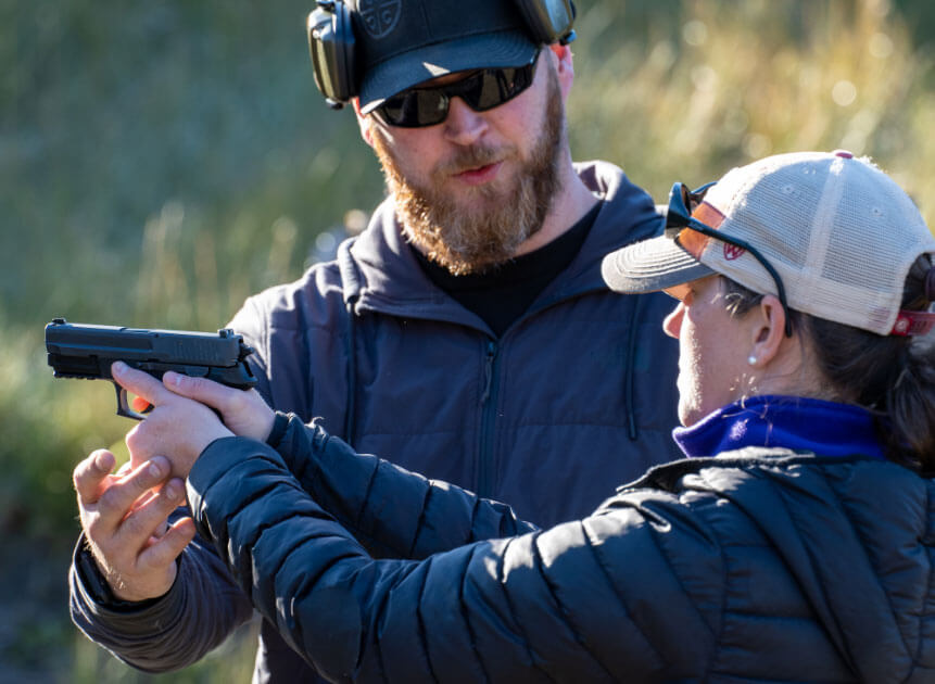 Gun safety instructor teaches woman with handgun at Alaska Tactical